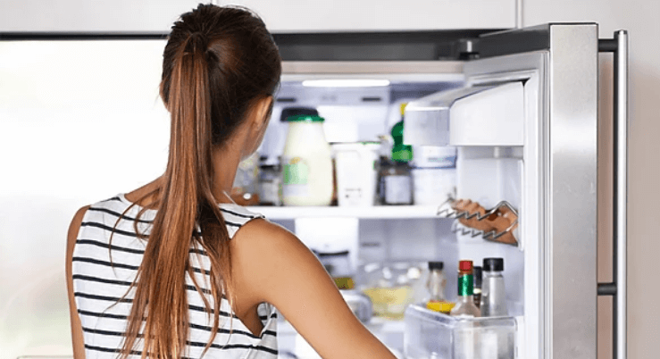 Woman Staring at Open Fridge of Food and Drinks